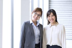 オフィスビルのロビーで立つ2人のビジネス女性の写真素材 [FYI02968042]