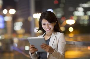夜の街を背景にタブレットPCを見て微笑むビジネス女性の写真素材 [FYI02968046]