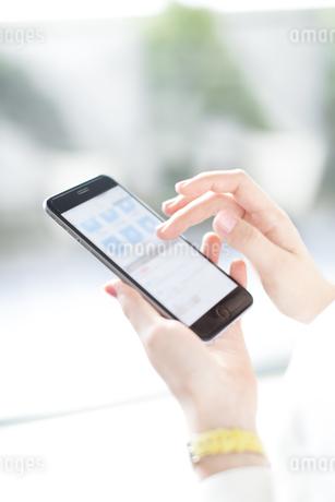 スマートフォンを操作するビジネス女性の手元の写真素材 [FYI02968049]