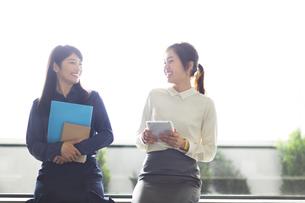 窓際に座って会話をするビジネス女性の写真素材 [FYI02968055]