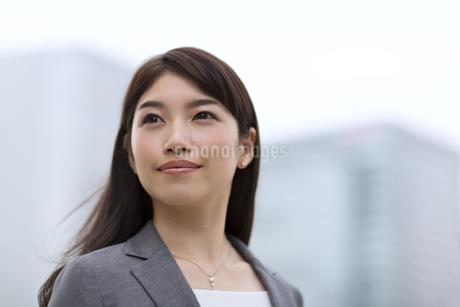 オフィスビルを背景に微笑むビジネス女性の写真素材 [FYI02968060]