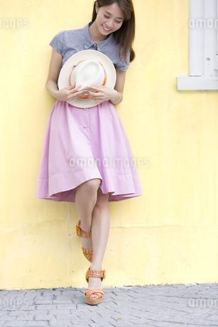 壁に寄り掛かって帽子を持って笑う女性の写真素材 [FYI02968061]