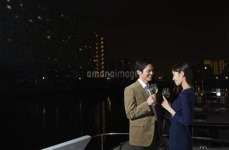 夜景をバックにワインを手に微笑むカップルの写真素材 [FYI02968062]