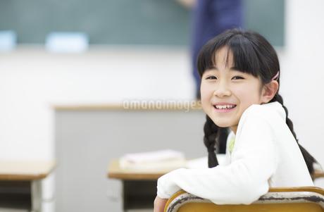 教室椅子に座って振り向く女の子の写真素材 [FYI02968063]