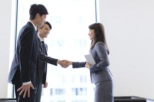 オフィスビルのロビーで握手をするビジネス男女の写真素材 [FYI02968065]