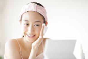 鏡の前で頬にコットンをあてスキンケアをする女性の写真素材 [FYI02968066]