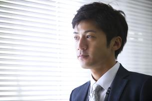 オフィスの窓際で立つビジネス男性の写真素材 [FYI02968068]