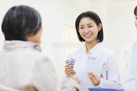 薬の説明をする女性薬剤師と患者の写真素材 [FYI02968073]
