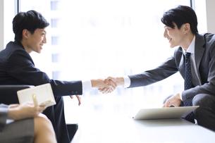オフィスビルのロビーで握手をするビジネス男性の写真素材 [FYI02968076]