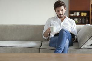 ソファーに座りカップを手に持って本を読む男性の写真素材 [FYI02968078]