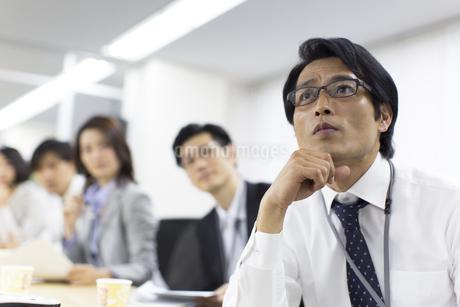 会議で話を聞くビジネス男性とスタッフの写真素材 [FYI02968080]