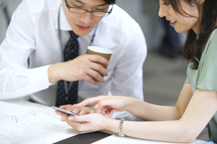 スマートフォンを使って打ち合せをするビジネス男女の写真素材 [FYI02968082]