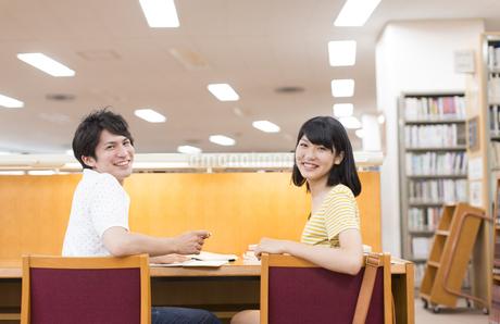 図書室のイスに肘をかけて笑う2人の学生の写真素材 [FYI02968083]