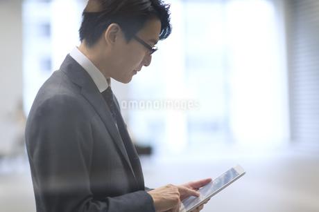 タブレットPCを見るビジネス男性の横顔の写真素材 [FYI02968084]