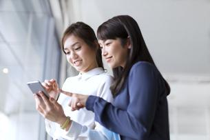 スマートフォンを見る2人のビジネス女性の写真素材 [FYI02968086]