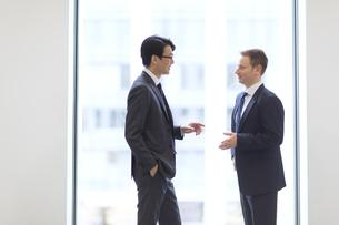 窓際で向かい合って会話をするビジネス男性の写真素材 [FYI02968091]