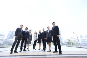 オフィスビルを背景に上を見上げて立つビジネス男女の写真素材 [FYI02968094]