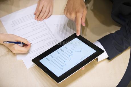 タブレットPCを持ち打ち合せをするビジネス男性の手元の写真素材 [FYI02968096]
