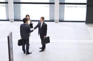 オフィスビルのエントランスで立って握手をするビジネス男女の写真素材 [FYI02968099]