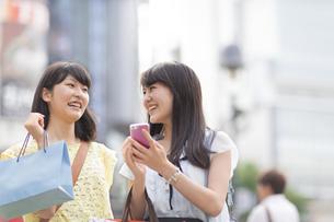 スマートフォンを持って歩く買物中の若い女性2人の写真素材 [FYI02968102]
