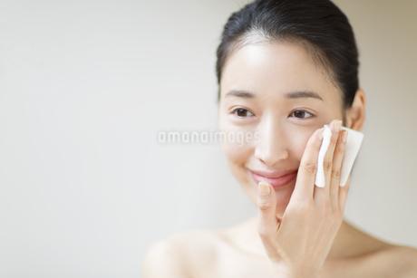 頬にコットンをあてスキンケアをする女性の写真素材 [FYI02968110]