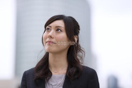 オフィスビルを背景に上を見上げるビジネス女性の写真素材 [FYI02968111]