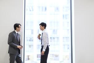 窓際で向かい合って会話をするビジネス男性の写真素材 [FYI02968113]