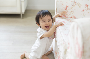 ソファーに寄りかかって笑う赤ちゃんの写真素材 [FYI02968114]