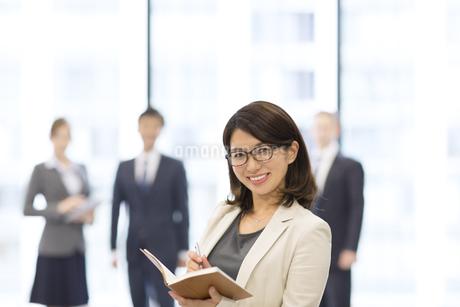 オフィスビルのロビーでノートを持って微笑むビジネス女性の写真素材 [FYI02968119]