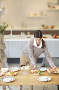 テーブルに食事を置く女性の写真素材 [FYI02968126]