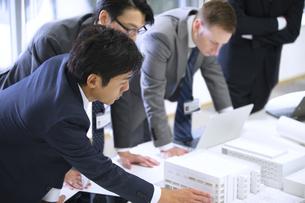 会議室で建築模型を使って打ち合せをするビジネス男性たちの写真素材 [FYI02968129]