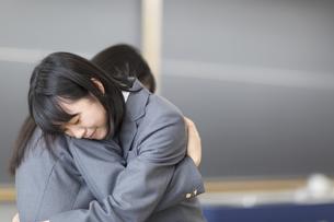 教室で抱き合う女子高校生の写真素材 [FYI02968130]
