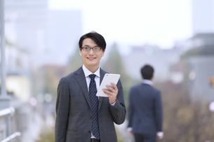 タブレットPCを持ち遠くを眺めるビジネス男性の写真素材 [FYI02968138]