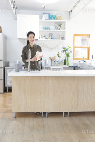 キッチンでコップを拭く女性の写真素材 [FYI02968147]