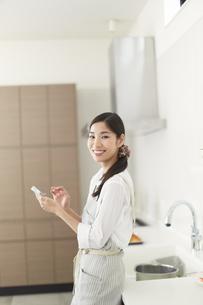 キッチンでスマートホンを持って微笑む主婦のスナップの写真素材 [FYI02968150]
