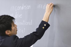 黒板に文字を書く男子学生の写真素材 [FYI02968151]