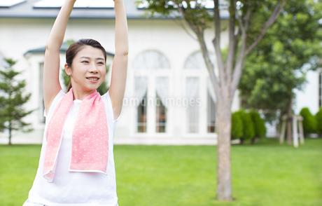 芝の上で伸びをする女性の写真素材 [FYI02968161]