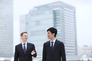 オフィスビルを背景に歩きながら話すビジネス男性2人の写真素材 [FYI02968171]