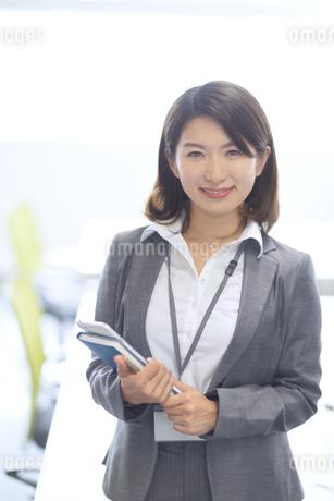 オフィスでタブレットPCと手帳を持って微笑むビジネス女性の写真素材 [FYI02968178]