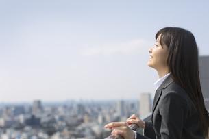 屋上で上を向いて微笑むビジネス女性の写真素材 [FYI02968181]