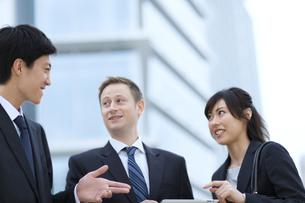 オフィスビルを背景に会話をするビジネス男女の写真素材 [FYI02968182]