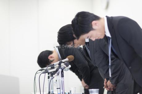 謝罪会見で頭を下げるビジネス男性3人の写真素材 [FYI02968187]