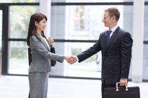 オフィスビルのエントランスで握手をするビジネス男女の写真素材 [FYI02968193]