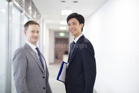 オフィスの廊下で微笑むビジネス男性2人の写真素材 [FYI02968194]
