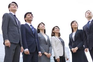 オフィスビルを背景に上を見上げて立つビジネス男女の写真素材 [FYI02968198]