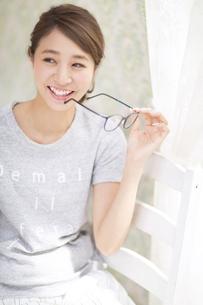 カーテンの傍で椅子に座り片手に眼鏡を持って笑う女性の写真素材 [FYI02968199]