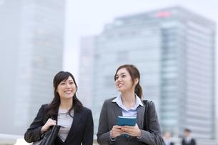 オフィスビルを背景に歩きながら話すビジネス女性2人の写真素材 [FYI02968204]