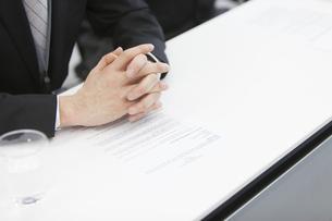 書類の上で組まれたビジネス男性の手の写真素材 [FYI02968206]
