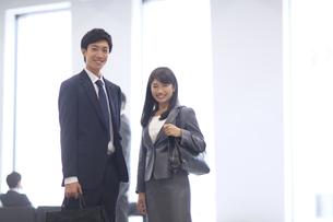 オフィスビルのロビーで立つビジネス男女の写真素材 [FYI02968208]