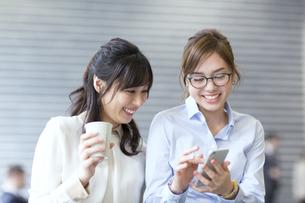 スマートフォンを見る2人のビジネス女性の写真素材 [FYI02968213]